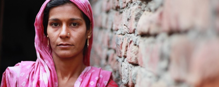 Indian woman leaning against a wall.