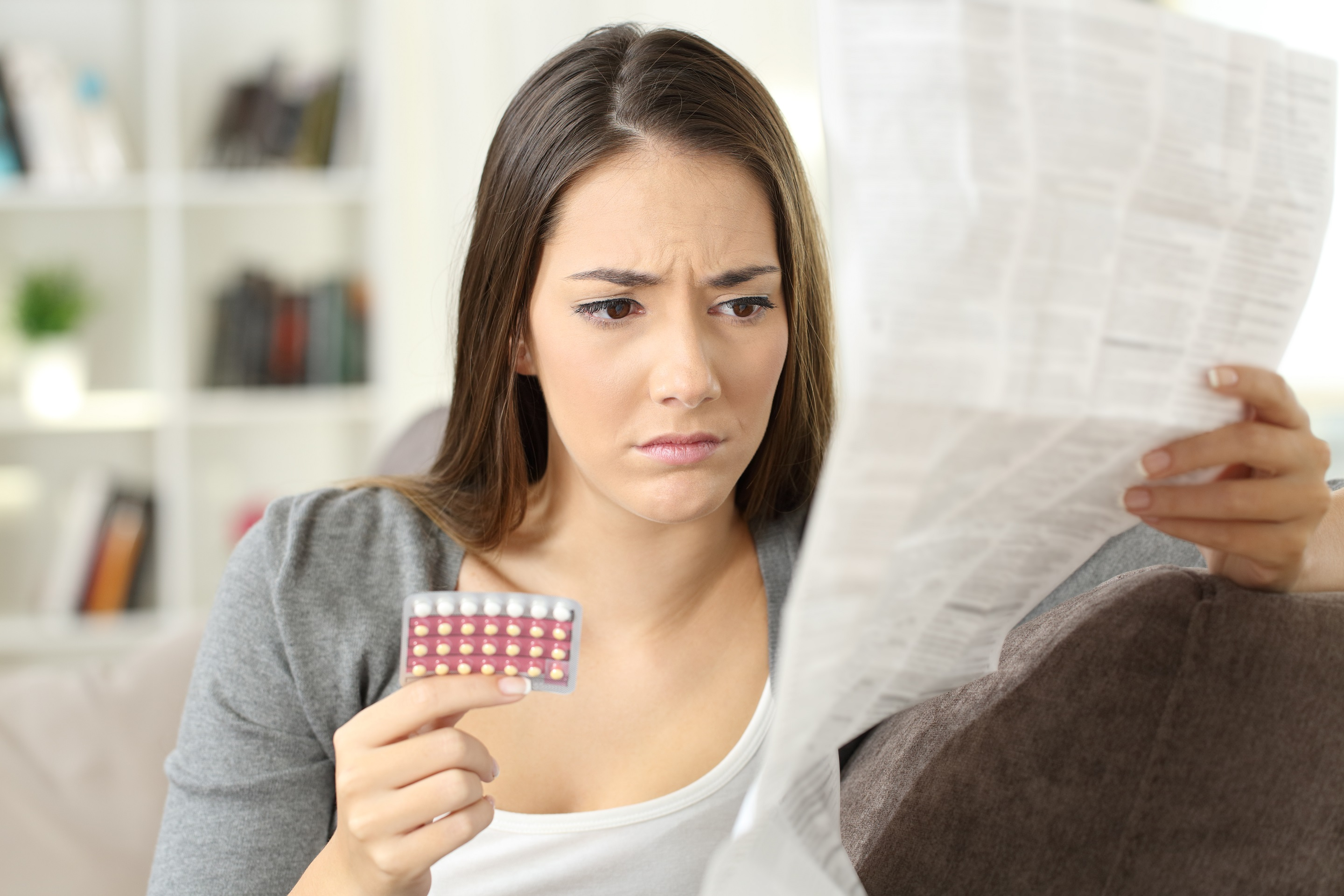 concerned woman reading pill leaflet