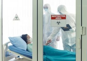 GettyImages-1207429695-scaled.jpg - Doctor examines corona or covid-19 virus patient in the clean room with covid 19 and restricted area sign in front of the room
